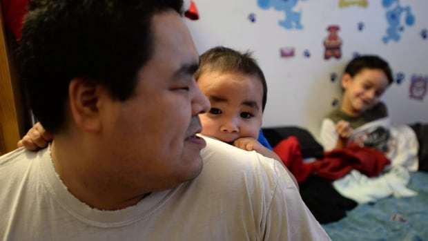 Israel Mablick, an Inuk father of five who can't afford food to feed his family, is seen at his home with his baby Israel Jr. in Iqaluit. Whether a solution can be found to the north's hunger issues is anyone's guess. After all, food shortages are nothing new to the Inuit.
