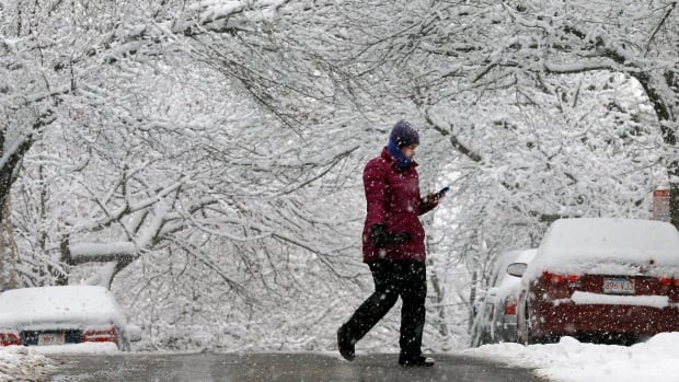 A woman crosses a road during a winter snowstorm in Somerville, Massachusetts on Saturday. Up to 20 centimetres of snow is expected to fall over parts of Atlantic Canada and northeastern U.S. this weekend.