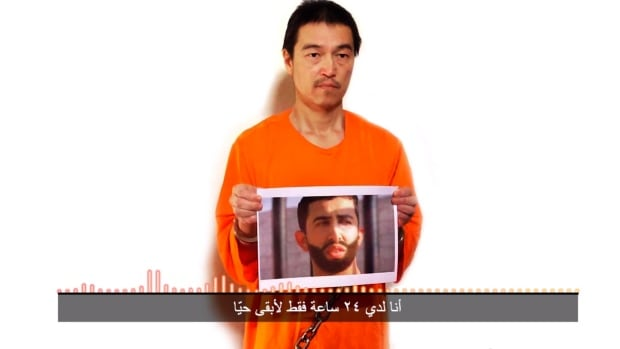 This image taken from a video posted on YouTube by jihadists on Tuesday shows a still photo of Japanese journalist Kenji Goto holding what appears to be a photo of Jordanian pilot 1st Lt. Mu'ath al-Kaseasbeh. Both are being held hostage by ISIS.