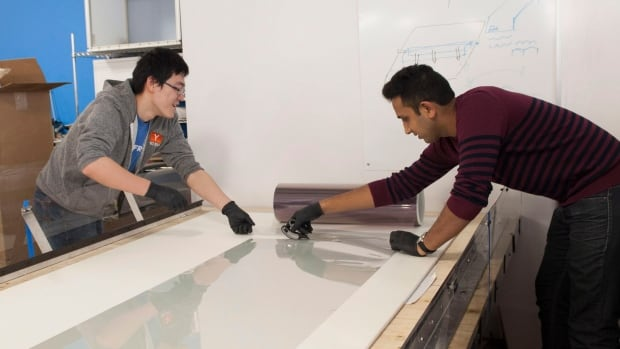 Neverfrost co-founders Chong Shen, left, and Khanjan Desai work in Kitchener, Ont., on with the infrared-reflective film they created. Neverfrost is designed to protect windshields by preventing frost during winters, and avoiding stone chips.