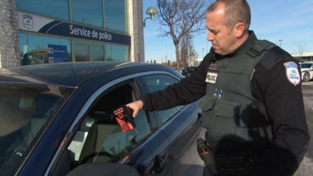A police officer in Gatineau, Que., uses a light meter to test the tint of a car window. A report coming before the Ottawa Police Services board on Monday will urge Ontario to match its rules with those that exist in Quebec.