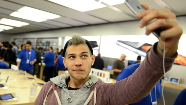 Toronto resident Dani Winters poses as he takes a selfie with a new iPhone at the iPhone 6 launch at the Eaton Centre's Apple Store. A Media Technology Monitor report suggests millennials, those aged 18 to 34, are using technology differently than older generations.