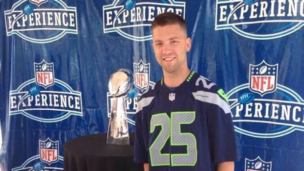 Diehard Seattle Seahawks fan Brendon Kuhn poses with the Lombardi Trophy, which the Seattle team won during at the 2014 Super Bowl.