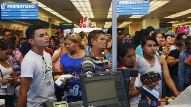 People queue up to make payment inside a Farmatodo drugstore in Caracas February 3, 2015.