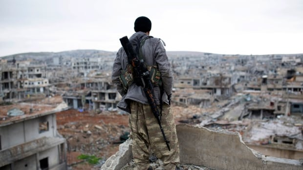 In this Jan. 30, 2015 file photo, a Syrian Kurdish sniper looks at the rubble in the Syrian city of Ain al-Arab, also known as Kobani. Foreign fighters are streaming in unprecedented numbers to Syria and Iraq to battle for ISIS or other radical groups, U.S. intelligence officials say.