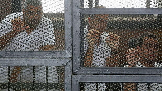 The three jailed Al Jazeera journalists, from left, Mohamed Fahmy, Peter Greste and Baher Mohammed stand behind bars at a court in Cairo in May 2014. Greste has since been released. Fahmy is to undergo retrial.