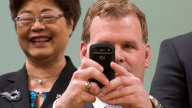 Minister of State (Seniors) Alice Wong looks on as Minister of Foreign Affairs John Baird takes a photo of photographers during a group photo following a ceremony at Rideau Hall in Ottawa on Monday, July 15, 2013.