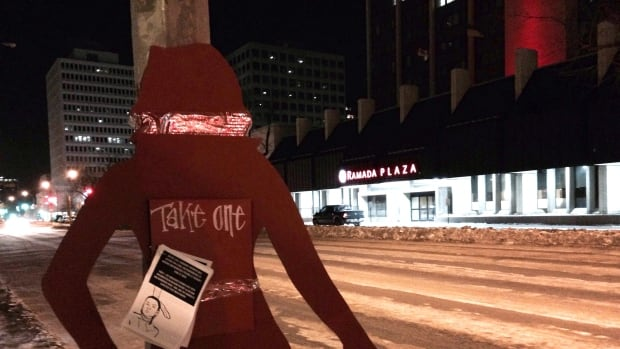 A red silhouette is seen near the corner of Victoria Avenue and Broad Street in Regina, raising awareness of a vigil in honour of Canada's missing and murdered indigenous women and people.