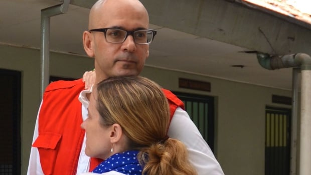 Neil Bantleman hugs his wife, Tracy, ahead of another day in court in Indonesia.