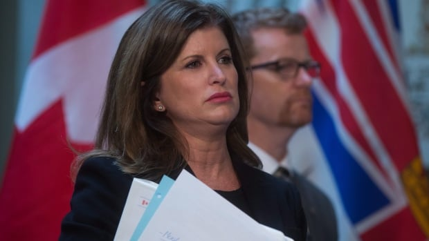 Federal Health Minister Rona Ambrose and B.C. Health Minister Terry Lake, back, listen to a question from a reporter last February. Ambrose has penned a sharply-worded letter calling for the provinces and territories to let the feds into their alliance working to slash the cost of prescription drugs.