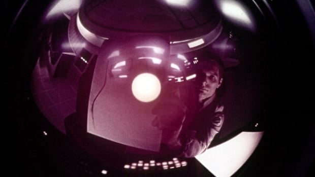 An astronaut looks at his reflection in a camera in a scene from the film '2001: A Space Odyssey', 1968.