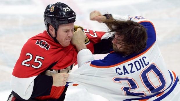 Ottawa Senators' Chris Neil, left, battles it out with Edmonton Oilers' Luke Gazdic during second period NHL hockey action in Ottawa on Saturday.