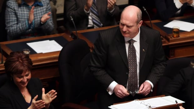 B.C. Finance Minister Mike de Jong, tables the budget in the Legislative Assembly in Victoria, B.C., Tuesday February 17, 2015 as Premier Christy Clark (left) applauds.