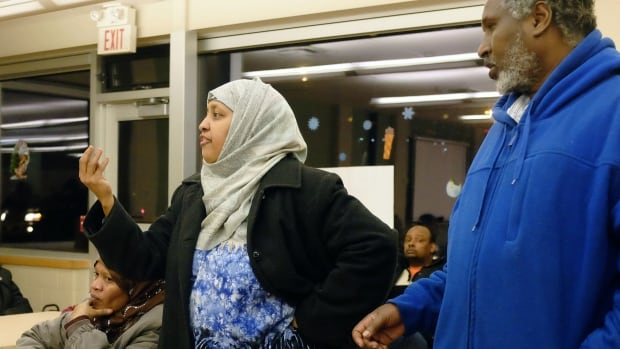 Interpreter Shanso Elmi, left, and 181 John St. N. resident Abdiwahid Omer speak out against the conditions in the building during a public meeting on Thursday evening.