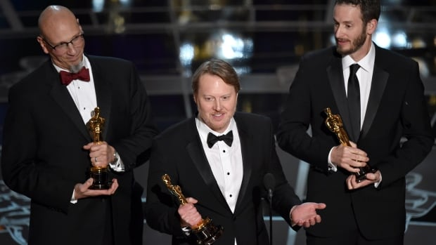 Roy Conli, from left, Don Hall, and Chris Williams  accept the award for best animated feature film for Big Hero 6 at the Oscars on Sunday at the Dolby Theatre in Los Angeles.