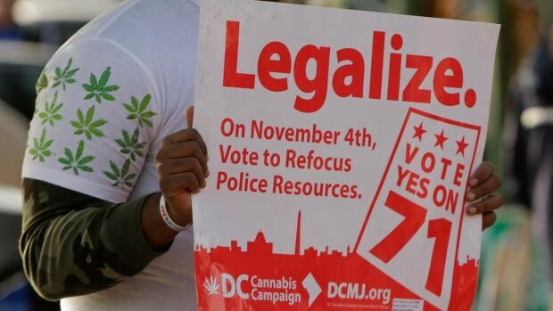 Melvin Clay of the D.C. Cannabis Campaign held a sign urging voters in the U.S. capital to legalize marijuana on election day on Nov. 4, 2014. The measure passed but Congress, which has control over local laws, is trying to block it.
