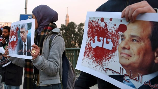 """Protesters hold posters of Egyptian President Abdel-Fattah el-Sissi and Interior Minister Mohamed Ibrahim with the word """"Killer"""" on them during a silent protest over a bridge in Cairo on Feb. 14."""