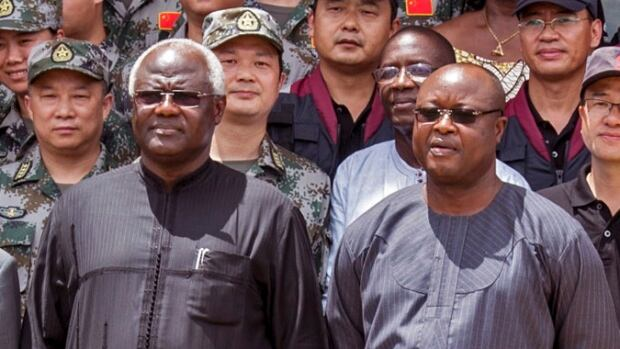 This Sept. 25, 2014 shows Sierra Leone's President Ernest Bai Koroma, left, and Vice President Samuel Sam-Sumana, right. Sam-Sumana has put himself in quarantine following the death from Ebola of one of his security guards.