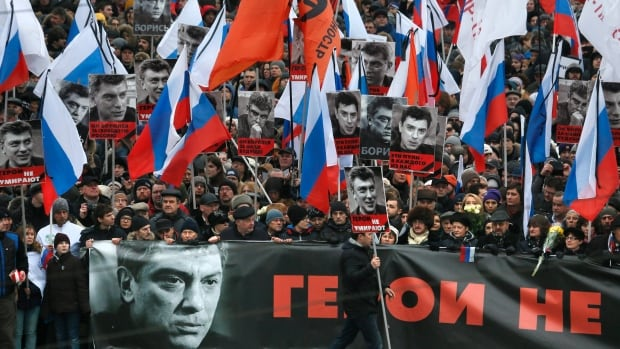 Russians carry a huge banner reading 'those bullets for everyone of us, heroes never die!' as they march in memory of opposition leader Boris Nemtsov in Moscow on Sunday. Tens of thousands converged in central Moscow and Saint Petersburg to mourn the veteran liberal politician.