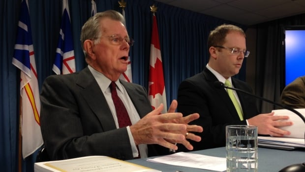 Commissioner Clyde Wells speaks with reporters Tuesday, as cabinet minister Steve Kent listens.