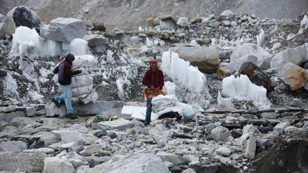 Garbage collectors collect rubbish at the deserted Everest base camp, approximately 5,300 metres above sea level, in Solukhumbu District on May 6, 2014.