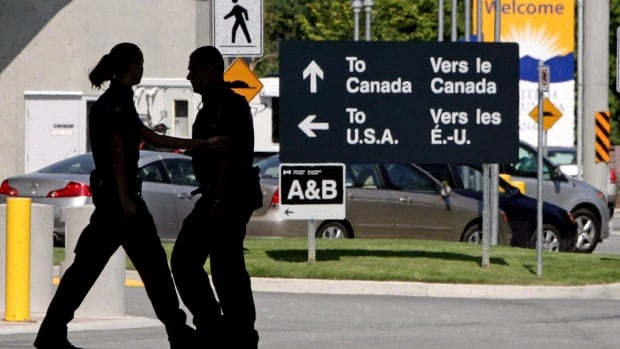 Canadian border guards are shown at an inspection booth at the Canada-U.S. crossing in Surrey, B.C. Car trips from the U.S. were up 5.4 per cent last year as the low Canadian dollar made Canada a bargain destination for Americans.