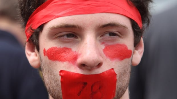 A protester with a painted face takes in a rally to mark the 100th day of the Quebec students strike, in Montreal, Tuesday, May 22, 2012.