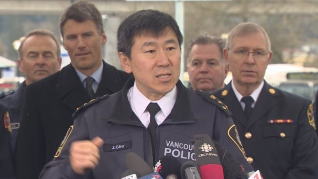 """Vancouver police chief Jim Chu, flanked by Vancouver mayor Gregor Robertson and Surrey fire chief Len Garis, speaks in favour of voting """"Yes"""" in the transit referendum."""