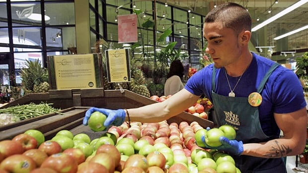 An employee at Whole Foods stocks apples in the produce section. The eco-minded chain has been accused of overcharging customers by mislabelling weights on prepackaged goods.