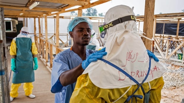A health-care worker prepares a colleague's Ebola virus protective gear in Makeni, Sierra Leone. An American health-care worker has been transported to the U.S. after contracting the virus.
