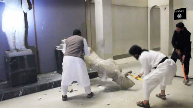 In this image made from video posted on a social media account affiliated with the Islamic State group on Thursday, Feb. 26, 2015, militants take sledgehammers to an ancient artifact in the Ninevah Museum in Mosul, Iraq.