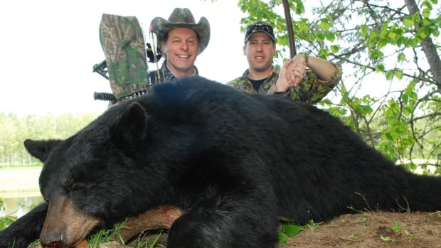 American rocker and hunter Ted Nugent is pictured with Christopher Dyer and the carcass of a black bear.