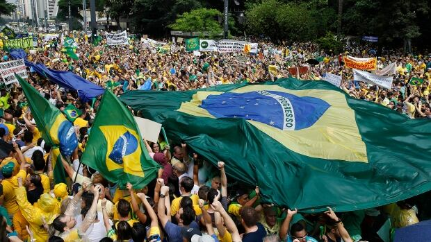 Demonstrators hold a Brazilian flag during a march in Sao Paulo on Sunday demanding the impeachment of President Dilma Rousseff.