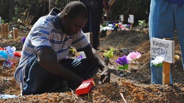 Stanley Juah, who survived exposure to Ebola, weeps at his son's grave in a cemetery for victims of the virus in Suakoko, Liberia.  Juah lost four of his family members and relatives in the outbreak.