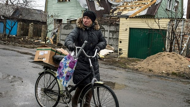 A woman pushes a bicycle past a destroyed house in the town of Debaltseve, northeast of Donetsk last week. Residents are hoping UN rations will keep them until gardens are ready.