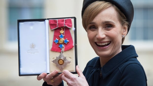 Actress Kristin Scott Thomas displays her Dame Commander of the British Empire medal presented to her by Britain's Queen Elizabeth II, at Buckingham Palace, in London, Thursday, March 19, 2015.