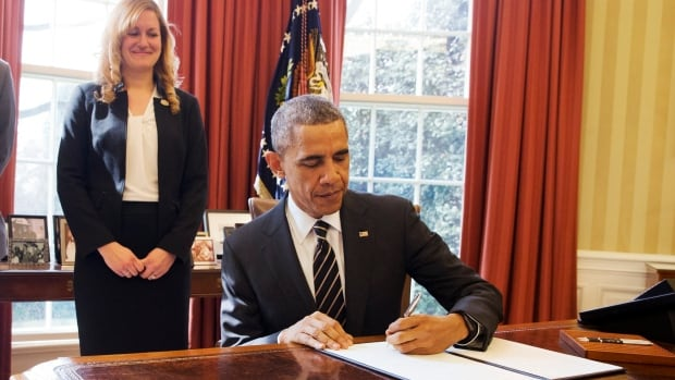 President Barack Obama signs an executive order, entitled Planning for Sustainability in the Next Decade, which will cut the federal government's greenhouse gas emissions over the next decade. Behind the president is Kate Brandt, federal chief sustainability officer.