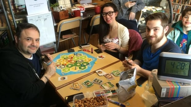 Matthew Baillie (far right) and Leah Burnell (centre) and Dan Ruimy are trying to break the world record for the longest board game ever played by playing Settlers of Catan.