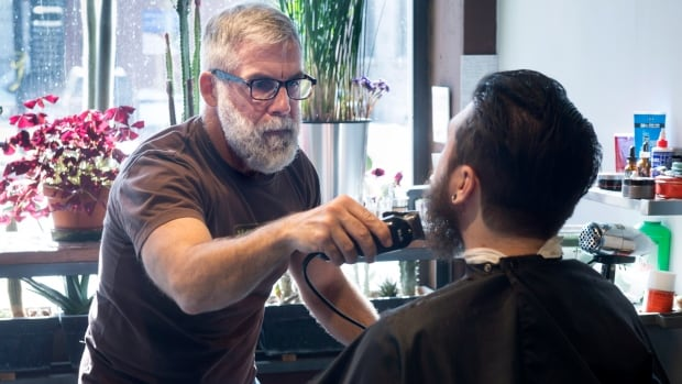 Jean-Marc Cardinal is seen in his barber shop Wednesday, March 4, 2015 in Montreal. Cardinal has owned and operated his barber shop, Mohawk Barbier Montreal, for 13 years, and said the village needs some new blood to help kickstart the local economy.