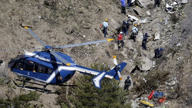 French gendarmes and investigators work amongst the debris of the Germanwings Flight 4U9525at the site of the crash, near Seyne-les-Alpes, French Alps.
