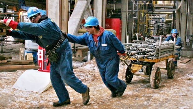 Workers in Fort McMurray move pipes at an oil facility. Canada's economy didn't expand at all in February, new data from Statistic Canada Thursday showed.