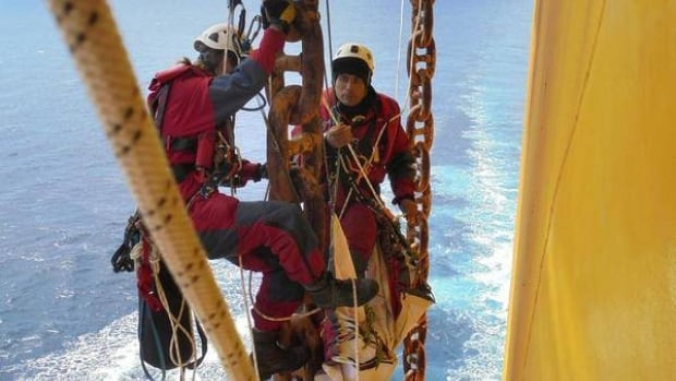 Greenpeace activists hang on a Shell oil rig on board the Blue Marlin, which is carrying the rig across the Pacific Ocean. Attorneys for Royal Dutch Shell PLC on Tuesday sued in federal court to remove six Greenpeace activists who boarded the vessel.