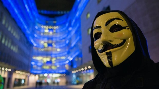 A supporter of the activist group Anonymous wears a mask during a protest in London in December 2014. The group's Quebec branch has claimed responsibility for cyber-attacks against the Montreal police and its union.