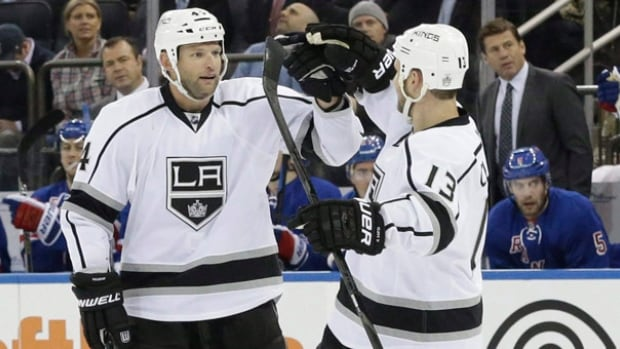 Los Angeles Kings defenseman Robyn Regehr, left, celebrates with forward Kyle Clifford after scoring a goal during a game in March.