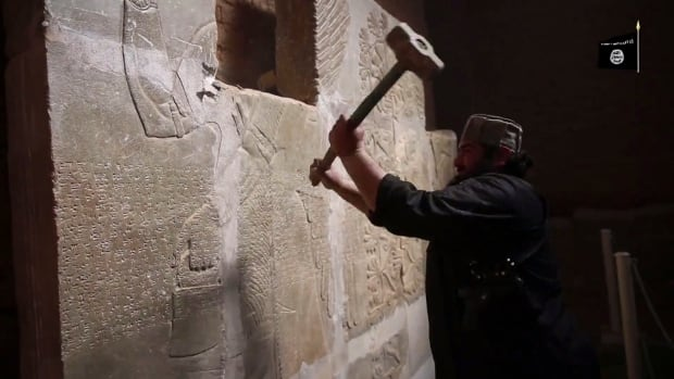 In this image made from video posted on a militant social media account affiliated with the Islamic State of Iraq and Syria (ISIS), a militant takes a sledgehammer to a relief at the site of the ancient Assyrian city of Nimrud.