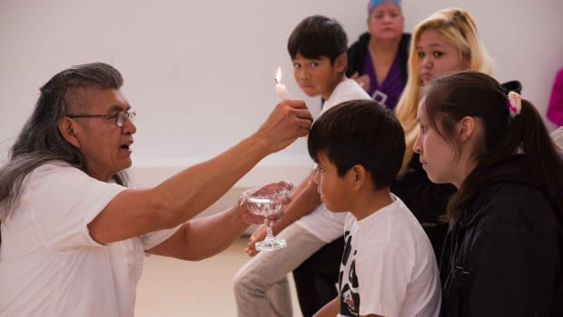 Eugene Harry baptises three children including twin boys at a Shaker ceremony in West Vancouver.