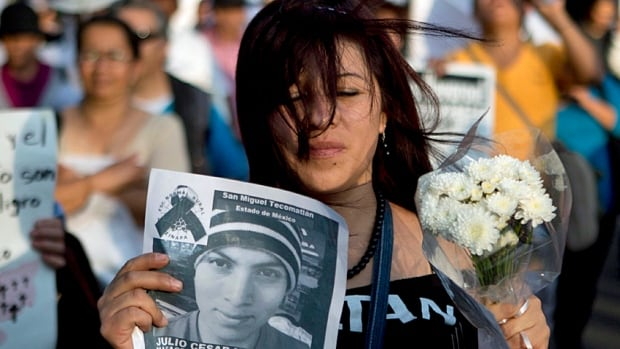 A demonstrator holds a photocopy of Julio Cesar Mondragon, one of the 43 missing students from a rural teachers' college, during one of the many protests that ripped through Mexico in the wake of the group's disappearance at the hands, it's reported, of local police and drug cartels last year.