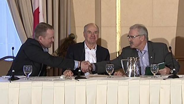 Karl Gerrand, CEO for G3 Global Grain Group, left, shakes hands with Agriculture Minister Gerry Ritz while CWB CEO Ian White looks on, at a news conference in Winnipeg Wednesday to announce G3 as the new majority investor in the CWB, formerly known as the Canadian Wheat Board.