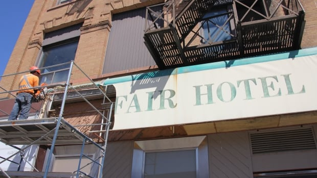 A worker takes down the sign outside the former Mayfair Hotel on King St. W. and Young St. in Kitchener in April 2014.