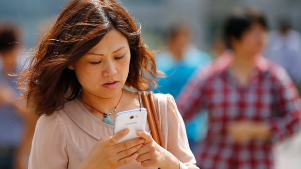 A woman looks at her smartphone as she walks on a busy street in downtown Shanghai. Google has been urging websites to cater to mobile device for years, mainly because that is where people are increasingly searching for information.